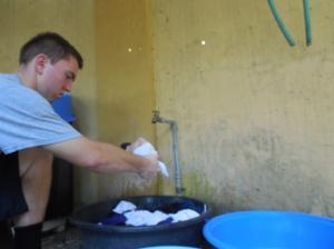 Elder Burbidge doing laundry in a bucket!
