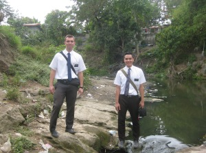 Elder Burbidge and Elder Baylon at a river near their area.
